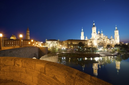 View of the  basilica of the Virgen del Pilar and Ebro river, on the left is located the medieval bridge called Puente de Piedra, Zaragoza, Aragon, Spain photo