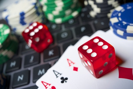 Casino chips, cards and dices stacking on a laptop photo