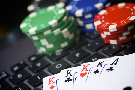 Casino chips and cards stacking on a laptop photo