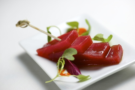 Red tuna in a small white saucer. photo