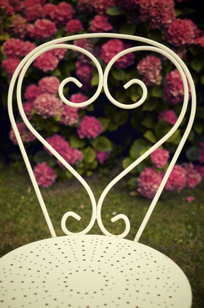 gentle dream vacation: Metal white chair view in a garden. Stock Photo