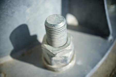 metal base: Close up of a larger screw into the base of a metal pillar. Stock Photo