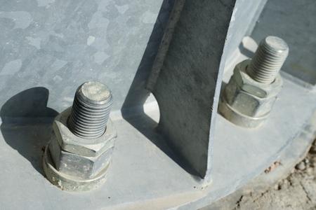metal base: Close up of some larger screws into the base of a metal pillar.