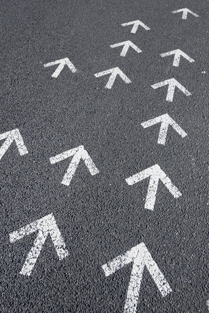 straight path: Directional arrows painted on a cement floor. Stock Photo
