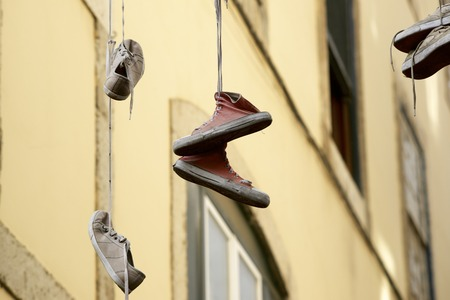 Old sneakers hanging from a cable. photo