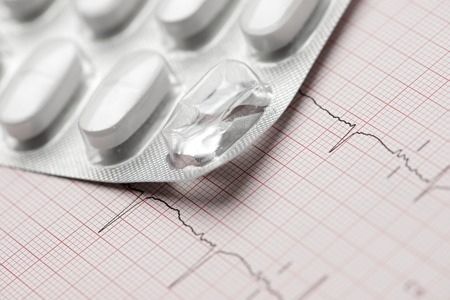 forefront: Forefront of a white medicine pills in blister pack and electrocardiogram.
