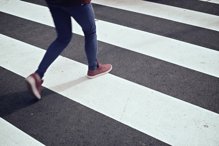 empty street: Young woman crossing a zebra crossing. Stock Photo