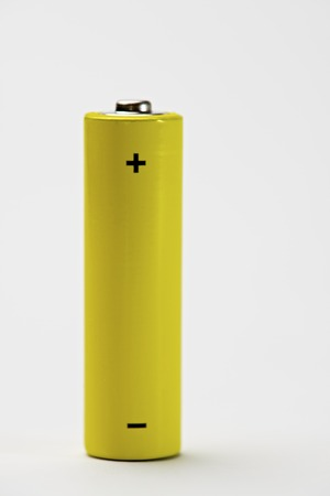 battery: Yellow battery on a white table.