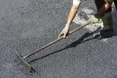 resurfacing: Worker at asphalting works a street. Stock Photo