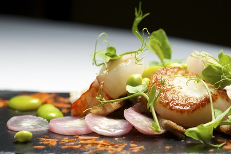 black dish: Piglet sauteed with scallops and prawns. Stock Photo