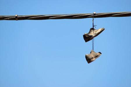 desprecio: Par de zapatos con estilo que cuelgan de un cable. Foto de archivo
