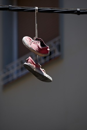 cable tangle: Old sneakers hanging from a cable.