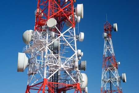 Telecommunications towers with clear blue sky.