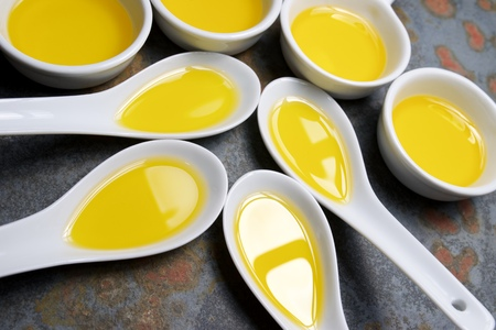 Olive oil in a small china spoons. Stock Photo