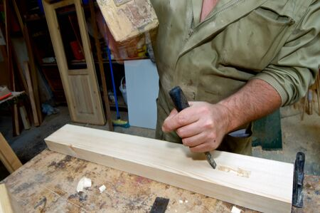 gouge: Forefront of the hands of a carpenter working.