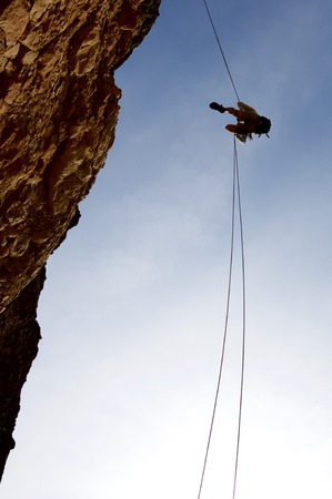 rappelling: climber descending with the technique of rappelling