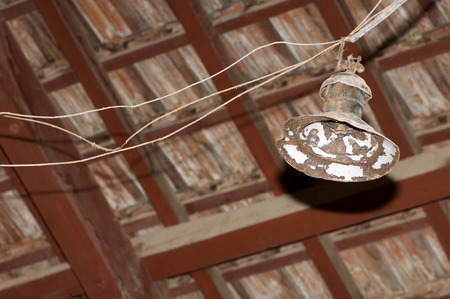 wooden  ceiling: Old lamp hanging from a wooden ceiling.