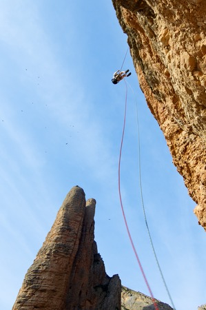 rappelling: climber descending with the technique of rappelling in Riglos mountains, Huesca, Aragon, Spain