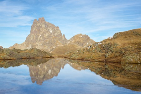 reflection: Midi Dossau Peak reflected in a lake. Ossau Valley, Pyrenees National Park, Pyrenees, France.