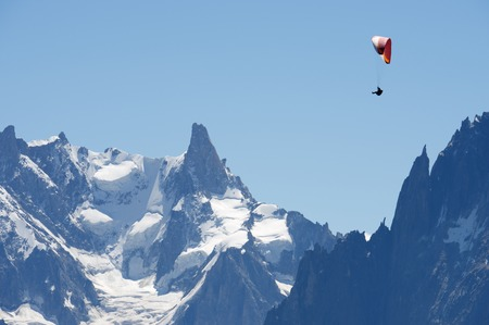 dent: Paragliding flying over Mont Blanc Massif, in the background is Dent du Geant, Alps, Chamonix, France Stock Photo