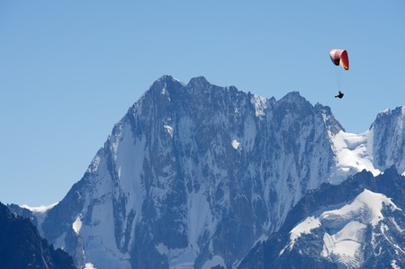 paraglide: Paragliding flying over Mont Blanc Massif, in the background is Grandes Jorasses peak, Alps, Chamonix, France Stock Photo