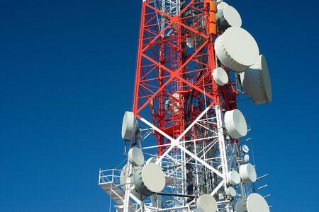 通信: Telecommunications tower with clear blue sky.