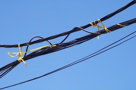 hassle: Electric cables tangled with blue sky. Stock Photo