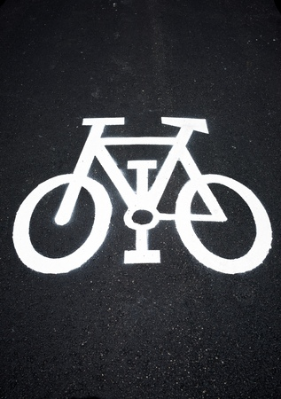 urbanism: Bike lane sign painted on a street.