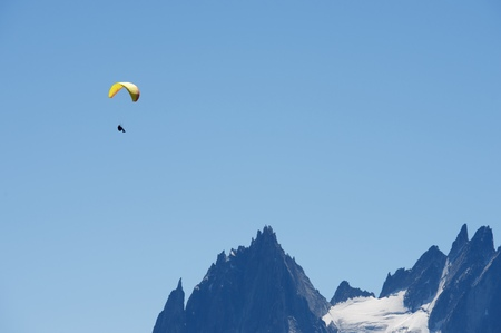 paraglide: Paragliding flying over Mont Blanc Massif, in the background are Aiguilles du Chamonix, Alps, Chamonix, France