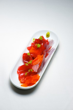 Red tuna in a small white saucer. Stock Photo