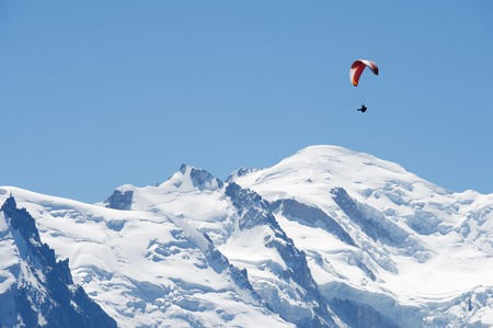paraglide: Paragliding flying over Mont Blanc Massif, in the background is Mont Blanc peak, Alps, Chamonix, France