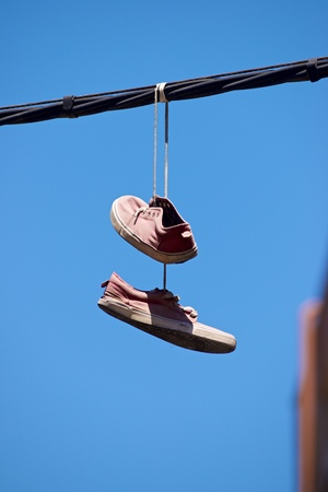 Old sneakers hanging from a cable.