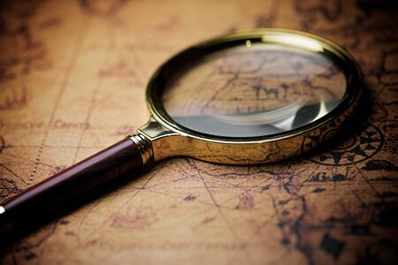 Magnifying glass and old navigation map.