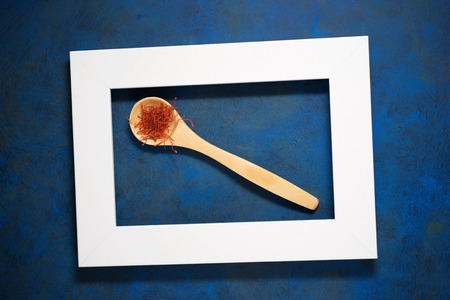 Saffron in a small wooden spoon.