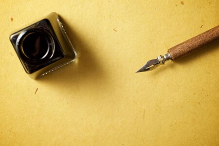 Nib pen for calligraphy and inkwell on a table. Stock Photo
