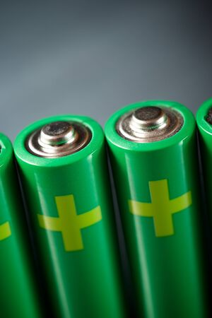 Four batteries on a metal table. Stock Photo