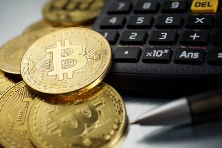 Bitcoins and a calculator on a metal table.