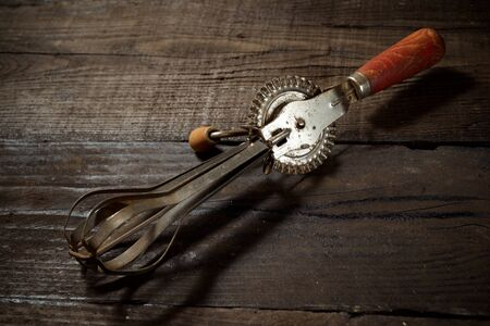 Old hand whisk on a wood table.