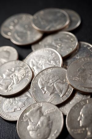 Quarter dollar coins on a black table