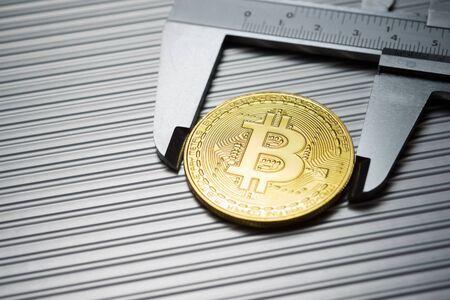 Bitcoin and caliper on a metal table. Foto de archivo
