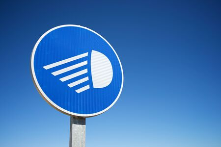 Traffic signal that indicates the obligatory nature of turning on the lights of the vehicle in Spain.