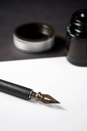 Nib pen for calligraphy and inkwell on a table.