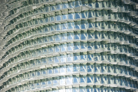 Zaragoza, Spain - November 16, 2017: Reflection on water of the skyscraper, named as Water Tower, is the tallest building in the city and an attraction of Expo 2008. Editorial