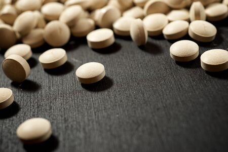 Beer yeast pills on a black table.