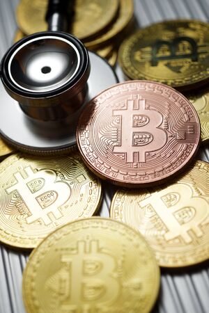 Bitcoins and stethoscope on a metal table.