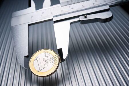 metal gauge measuring a one euro coin on a metal surface. Stok Fotoğraf