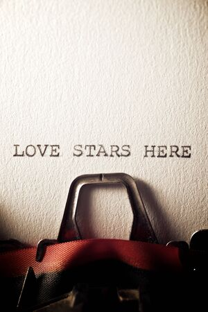 The sentence, Love Stars Here, written with a typewriter.