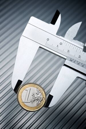 metal gauge measuring a one euro coin on a metal surface. Reklamní fotografie