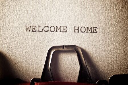 The sentence, Welcome Home, written with a typewriter.