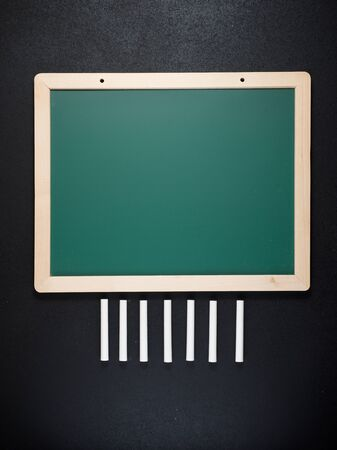 View of a group of chalks and a green blackboard. 版權商用圖片 - 138255557